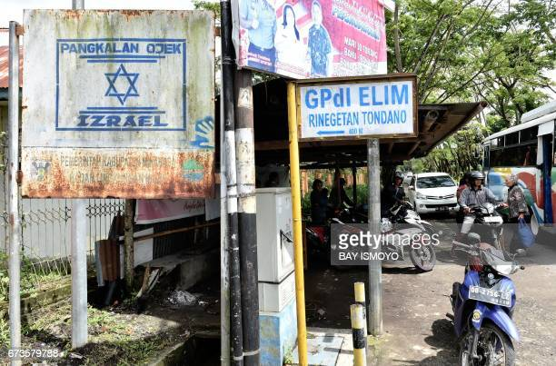 This photograph taken on February 17 2017 shows a sign for a motorcycle taxi pool named 'Izrael' with the Star of David in Tondano North Sulawesi In...