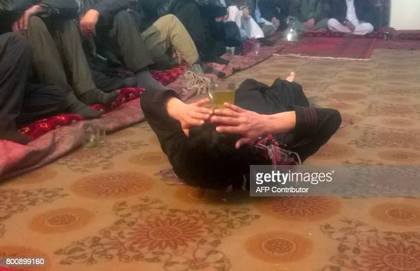 This photograph taken on February 18 2017 shows an Afghan youth dancing at a private party in an unidentified location in Afghanistan Bacha bazi is...