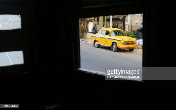 This photograph taken on February 21 shows a view from a tram as a Hindustan Motors Ambassador car drives past on a street in Kolkata India's...