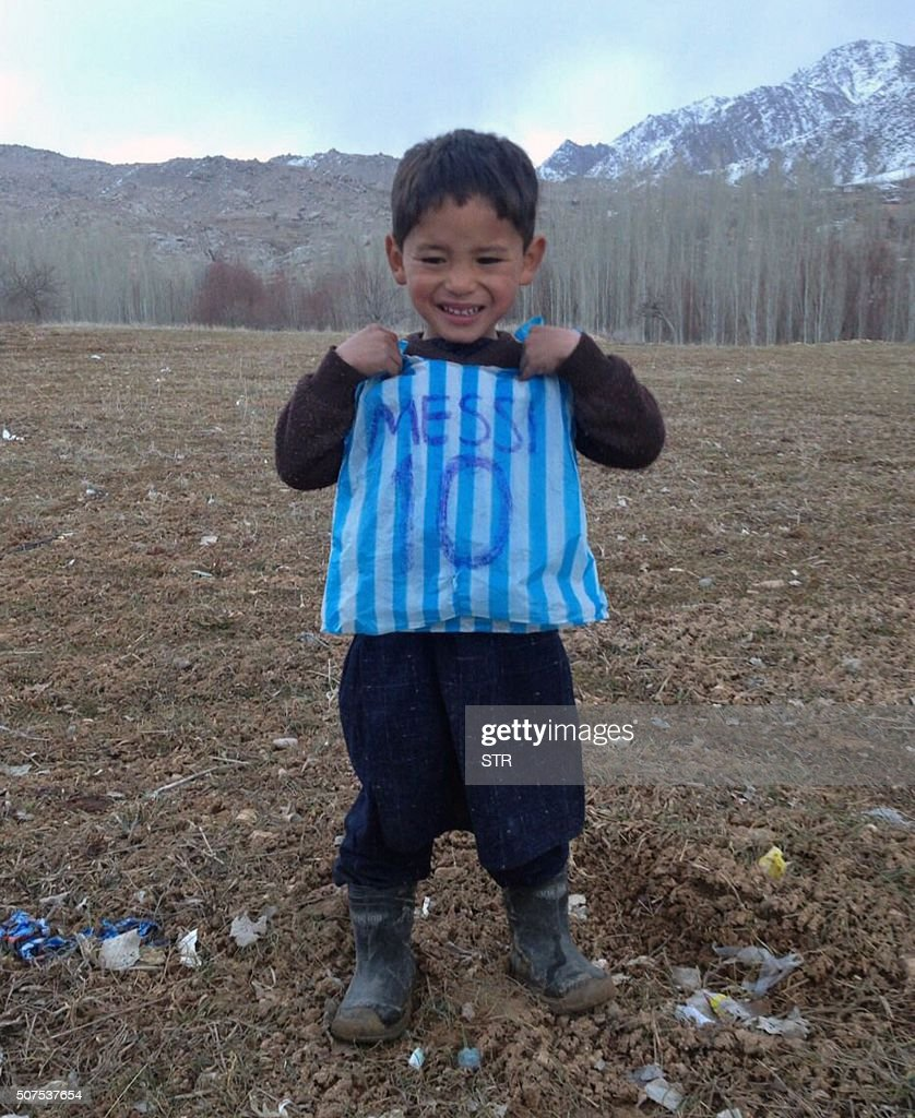 This photograph taken on January 24, 2016 and provided by the family of Afghan boy and Lionel Messi fan Murtaza Ahmadi, 5, with his plastic bag jersey in Jaghori district of Ghazni province. A five-year-old Afghan boy has become an internet star after pictures went viral of him wearing an Argentina football shirt made out of a plastic bag, complete with his hero Lionel Messi's name.