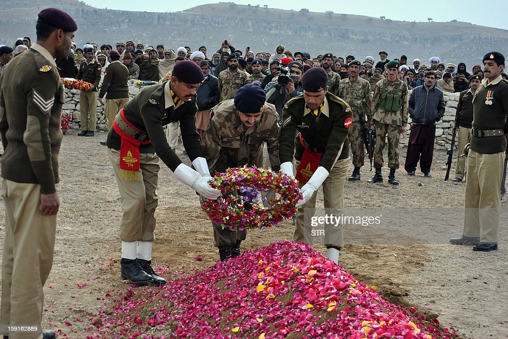 This photograph taken on January 8, 2013 Pakistani army officials lay a wreath on the grave of soldier Mohammad Aslam, who was killed during a border post attack in the Haji Pir sector of Pakistan-administered Kashmir by Indian soldiers, during his funeral in Khairpur village Chakwal district. Pakistani and Indian troops exchanged fire on January 6 along their hotly disputed border in divided Kashmir, with each side accusing the other of starting the clash. Pakistan on January 9 denied an Indian claim that its troops killed two Indian soldiers in a cross-border attack on January 8 that has raised tensions in South Asia, a military official said.