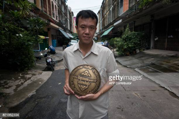 This photograph taken on July 12 2017 shows Thai dissident Ekachai Hongkangwan holding a brass replica of the missing plaque commemorating the year...