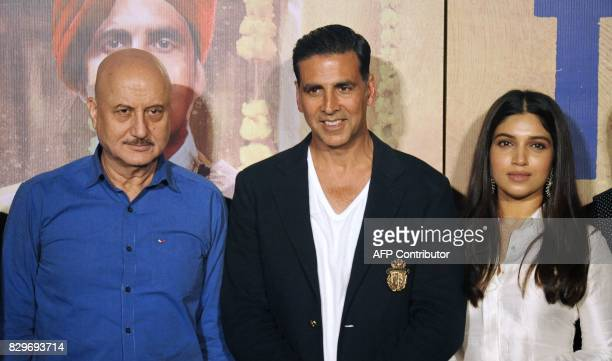 This photograph taken on July 27 2017 shows Indian Bollywood actors Anupam Kher Akshay Kumar and Bhumi Pednekar at a press conference for the Hindi...