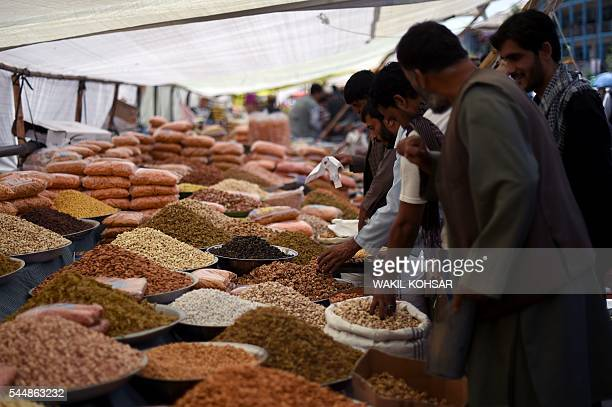 This photograph taken on July 3 2016 shows Afghan men buying dry fruits and nuts ahead of the Eidal Fitr festival which marks the end of Islamic holy...