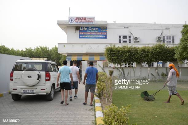 This photograph taken on June 12 shows Indian patients at the entrance to the Life Care Rehabilitation Centre on the outskirts of Jalandhar Opium...