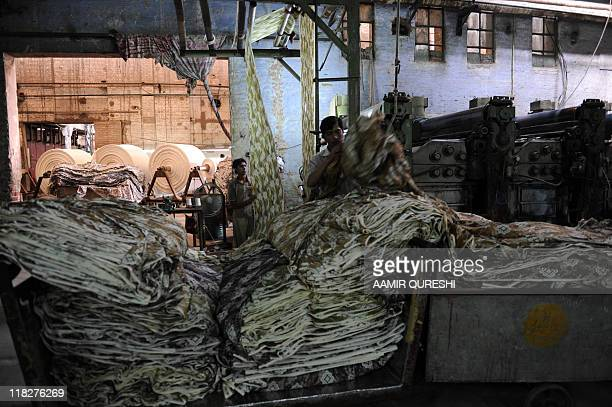 SHAHZAD This photograph taken on June 16 shows Pakistani employees at work at a textile factory in Faisalabad Spinning yarn into cloth has longbeen a...