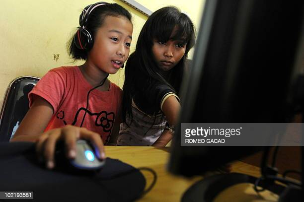 This photograph taken on June 17 2010 shows two Indonesian 12 year old teenage girls Vinna Erviliana and Mardiana online on Facebook at an Internet...