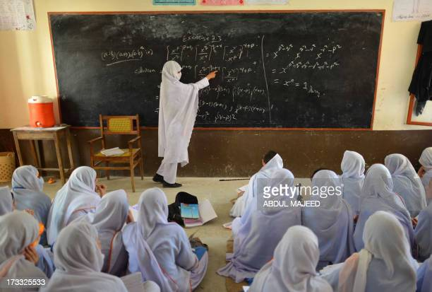This photograph taken on June 21 2013 shows a Pakistani teacher leading a class of girls at a school in Mingora the main town of Swat valley When the...