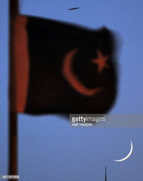 This photograph taken on June 29 shows the crescent moon signifying the start of the Islamic holy month of Ramadan under Pakistan's national flag in...