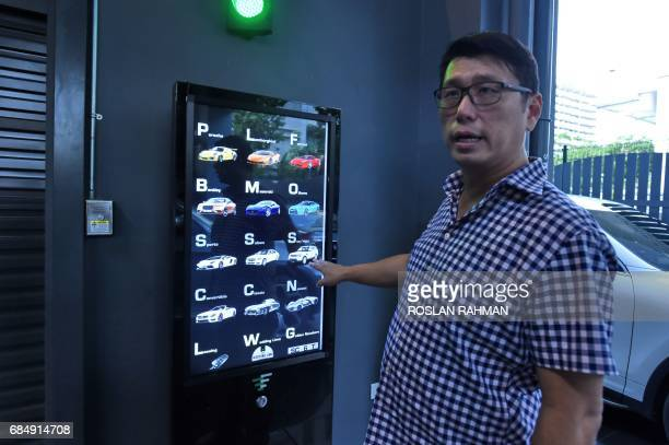 This photograph taken on May 18 2017 shows used car dealer Gary Hong showing the selection buttons for luxury supercars displayed inside the AutoBahn...
