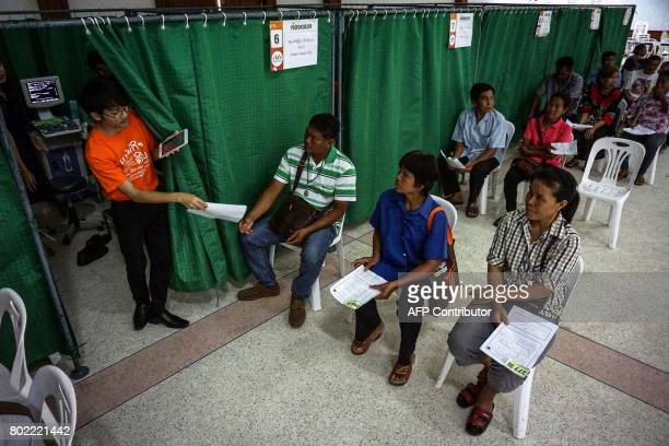 This photograph taken on May 19 2017 shows a health worker taking registration papers from a patient during a CASCAP event in the northeastern Thai...