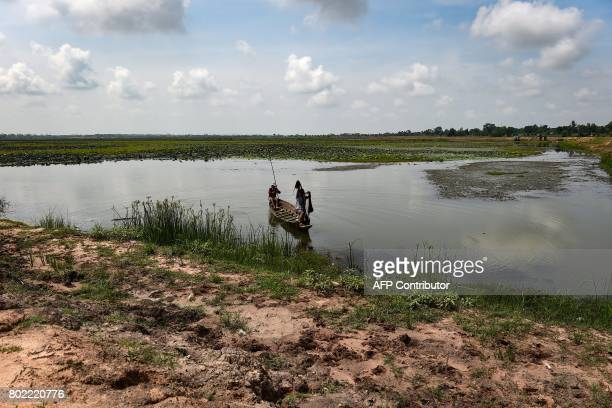 This photograph taken on May 20 2017 shows farmers fishing in a lotus lake in the northeastern Thai province of Khon Kaen Millions of Thais across...