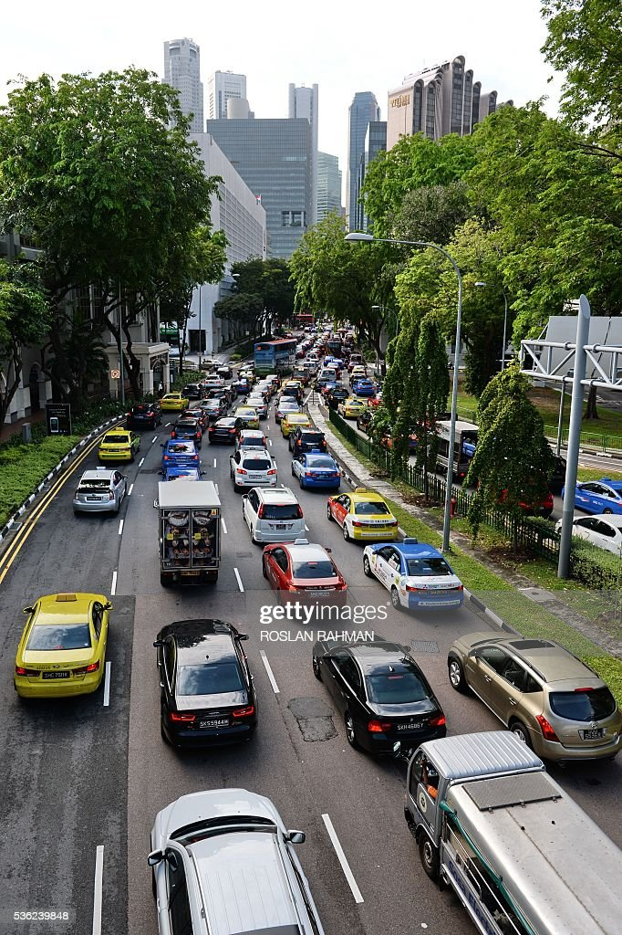 This photograph taken on May 31, 2016 show heavy traffic as motorists enter the central business district during morning peak period in Singapore. / AFP / ROSLAN