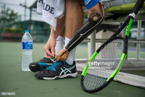 This photograph taken on May 31 2017 shows tennis player Alex Hunt tying the laces on his tennis shoes before a training session with his coach in...