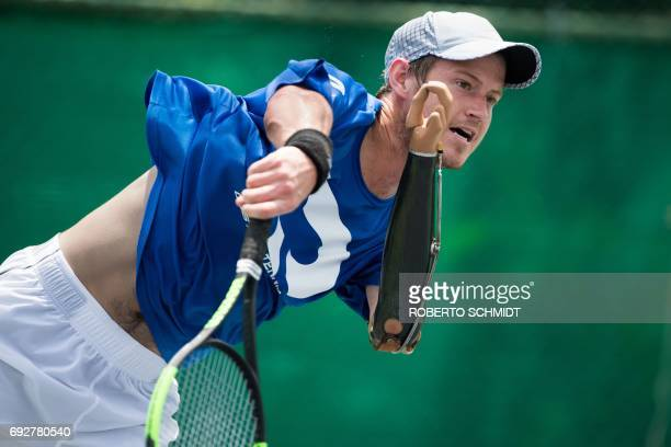 This photograph taken on May 31 2017 shows tennis player Alex Hunt following through on his serve during a training session with his coach in Bangkok...