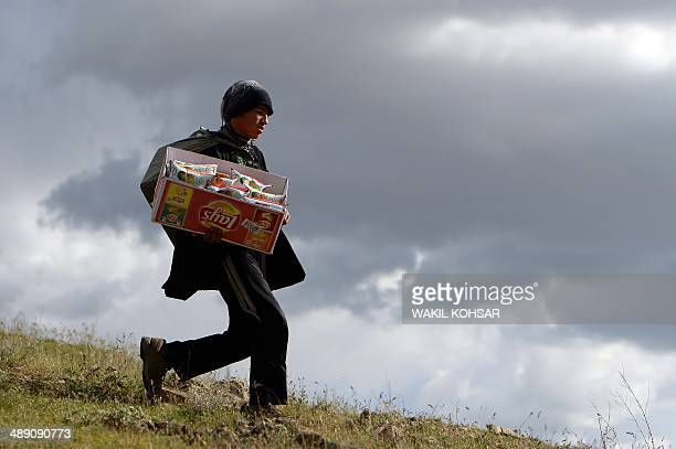 This photograph taken on May 9 2014 shows 16year old street vendor Hussain as he sells snacks on a hilltop near Qargha Lake in the outskirts of Kabul...
