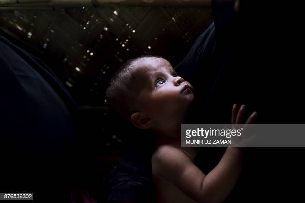 This photograph taken on November 16 2017 shows a young Rohingya Muslim refugee boy suffering from malnutrition looking on at the center for the...