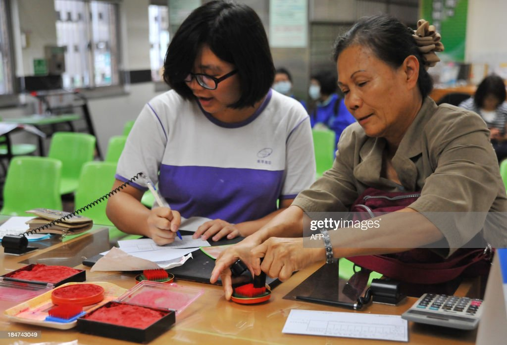 This photograph taken on October 15, 2013 shows customers preparing application forms at a post office in Taipei. AFP PHOTO / Mandy CHENG