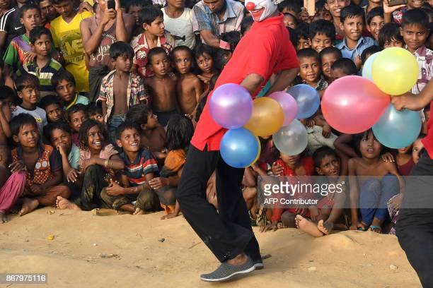 This photograph taken on October 28 2017 shows Rohingya refugee children watching the Bangladeshi theatre group 'Drama Therapy' at Kutupalong refugee...