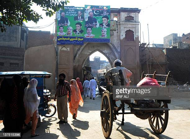 This photograph taken on October 29 2011 shows people entering through a gate to the walled city in Lahore The medieval walled city of Lahore is...
