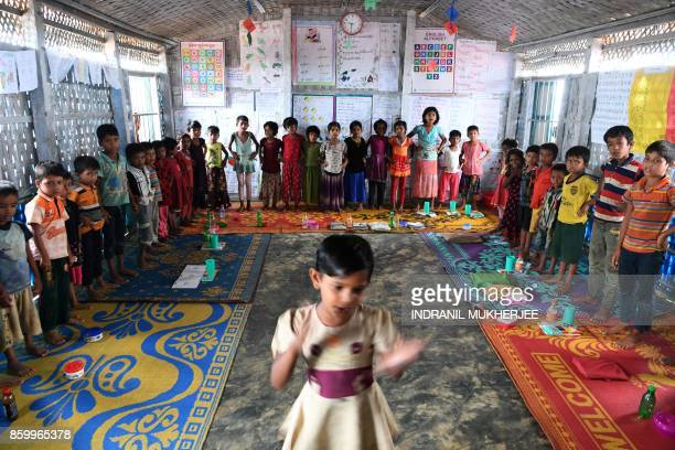 This photograph taken on October 7 2017 shows Rohingya refugee children looking at a classmate during an activity at a school in Kutupalong refugee...