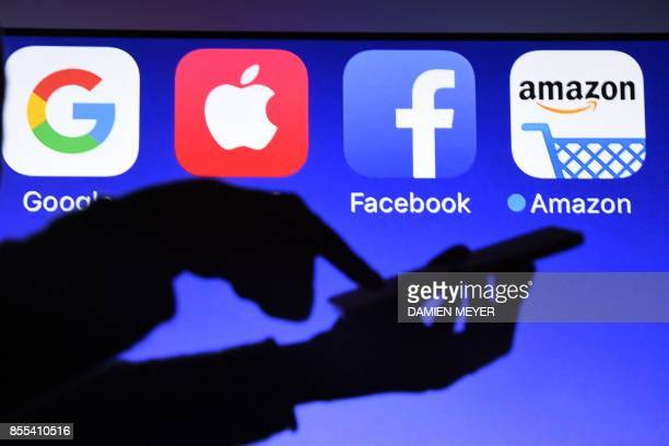 This photograph taken on September 28 shows a smartphone being operated in front of GAFA logos as background in HédéBazouges western France / AFP...