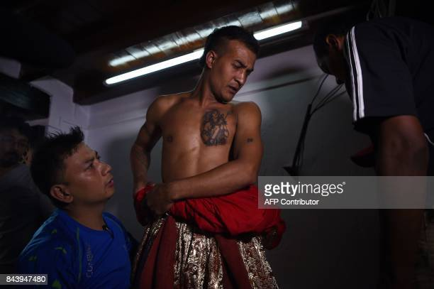 This photograph taken on September 3 2017 shows Nepali Lakhe dancer Laxman Ranjit being helped into his costume before performing the 'Lakhe' dance...