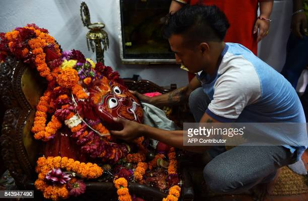 This photograph taken on September 3 2017 shows Nepali Lakhe dancer Laxman Ranjit cleaning a mask before performing the 'Lakhe' dance in Kathmandu...
