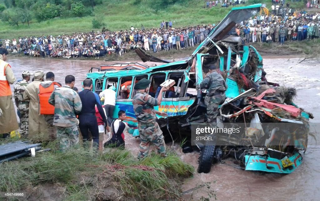 This photograph taken on September 4 2014 and received late September 5 shows rescue workers recovering the wreckage of a bus that was swept away by...