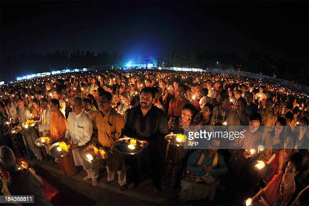 This photograph taken with a fisheye lens shows thousands of Indian Hindu devotees light candles in the form of the 'Aum' religious symbol during a...