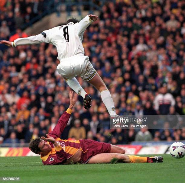 This picture can only be used within the context of an editorial feature Bradford City's Lee Sharpe watches as Leeds United's Michael Bridges hurdles...