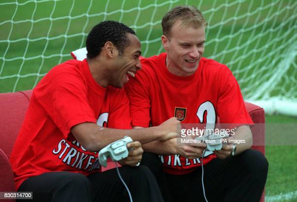This picture can only be used within the context of an editorial feature Arsenal soccer stars Dennis Bergkamp and Thierry Henry play Virtua Striker 2...