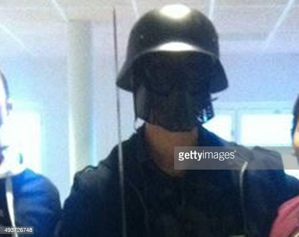 This picture made available to AFP by a student shows the masked man armed with a sword posing for a photo with two other students before attacking...