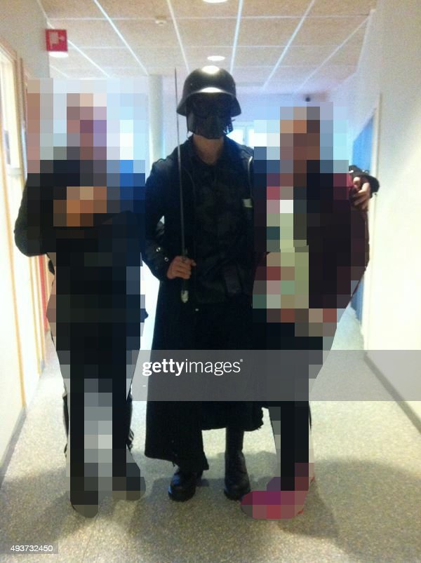 NEW VERSION This picture made available to AFP by a student shows the masked man armed with a sword posing for a photo with two other students before...