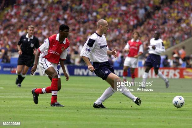 This picture may only be used within the context of an editorial feature Arsenal's Kanu watches as Manchester United's Jaap Stam passes the ball...