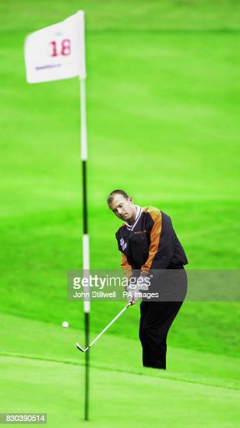 This picture may only be used within the context of an editorial feature England football captain Alan Shearer plays a chip shot onto the 18th green...