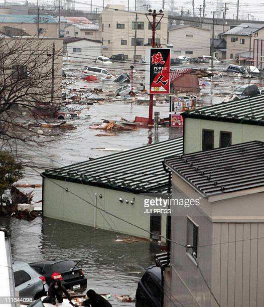 This picture offered from Shiogama City resident Akira Shibahara and taken on March 11 2011 shows people looking at a tsunami wave engulfing vehicles...