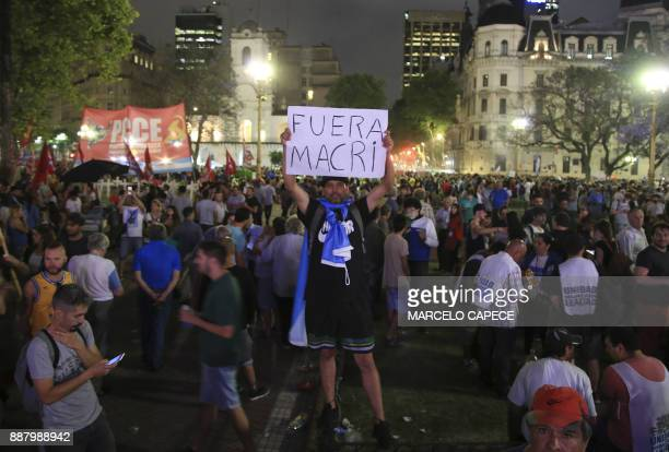 This picture released by Noticias Argentinas shows a demonstrator holding a sign reading 'Macri Out' during a demonstration by members of political...