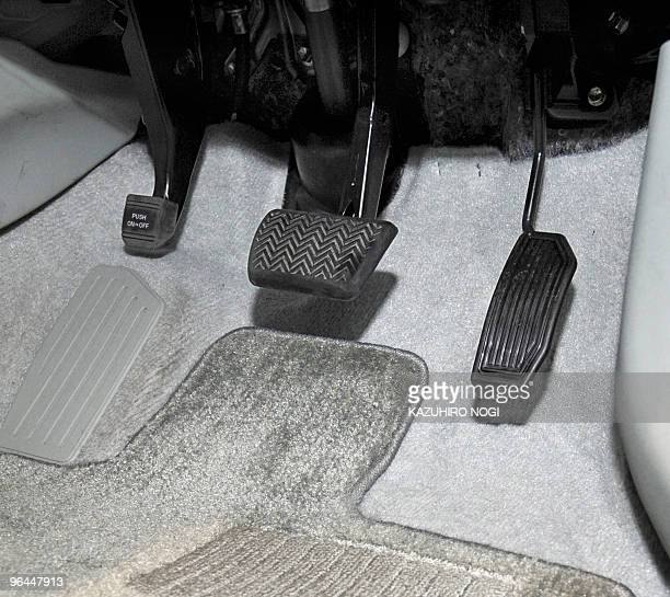 This picture shows a brake pedal and an accelerator of the latest Toyota Prius hybrid vehicle on display at the company's showroom in Tokyo on...
