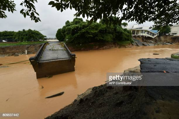 This picture shows a damaged bridge and Hiramatsu Junior High School following heavy flooding in Asakura Fukuoka prefecture on July 6 2017 At least...
