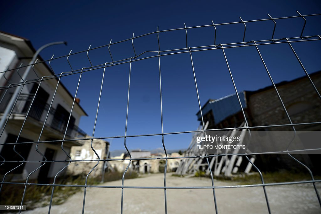 This picture shows a fence blocking the entrance near damaged buildings following the 2009 earthquake on October 22 2012 in the village of Onna Six...
