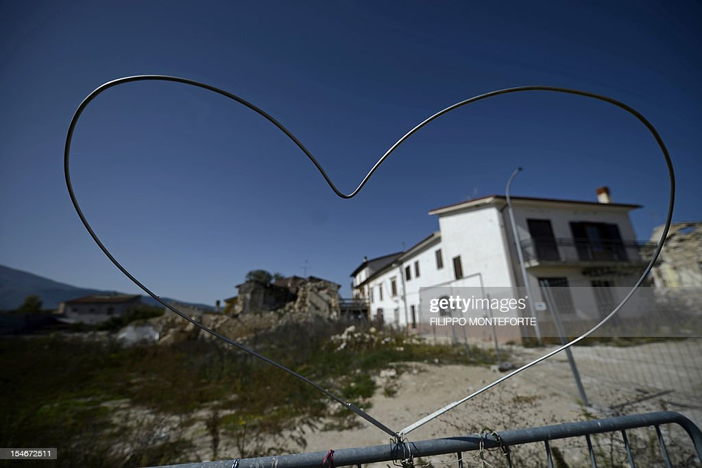 This picture shows a heart sculpted in metal wire in front of damaged buildings following the 2009 earthquake on October 22 2012 in the village of...