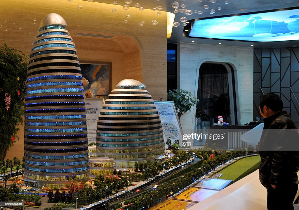This picture shows a man looking at a model of the Meiquan 22nd Century building in China's southwest Chongqing on January 3, 2012. Already famed for fake designer bags and pirated DVDs, imitation in China may have reached new heights with a set of towers that strongly resemble ones designed by renowned architect Zaha Hadid. It could rank among the more flagrant ripoffs in a country already notorious for imitating foreign products without permission -- but the developer of the Chongqing project, Meiquan 22nd Century, has denied any copying. CHINA