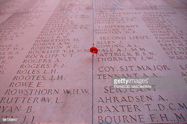 This picture shows a poppy stuck on a memorial wall during a dawn service commemorating Anzac Day on the WWI battlefield of VillersBretonneux...
