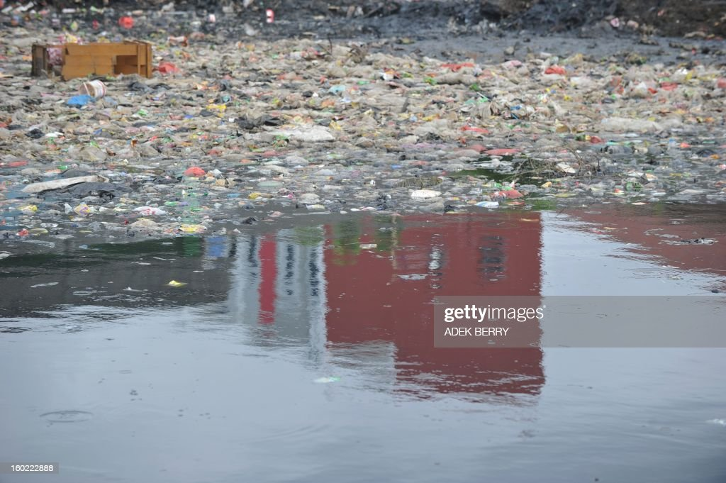 This picture shows a reflection of a building seen the polluted Pluit dam in Jakarta on January 28, 2013. AFP PHOTO / ADEK BERRY