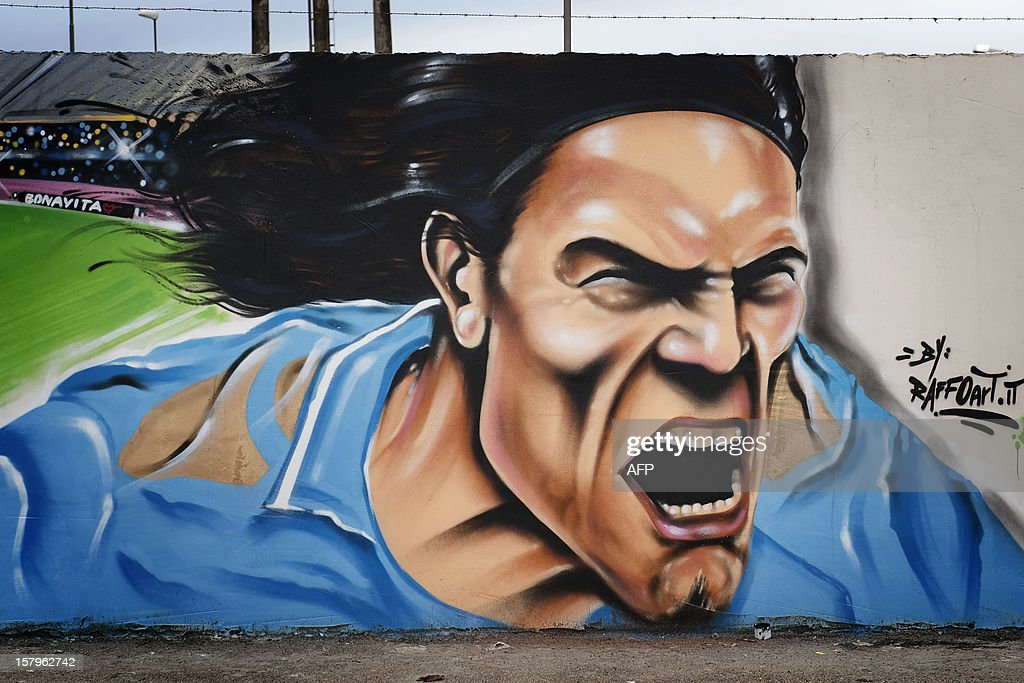 This picture shows a seven-meter mural painting by Napolitan artist Raffo depicting SSC Napoli's Uruguayan forward Edinson Cavani on December 8, 2012 in Volla near Naples. Raffo is a well known street artist in Naples. AFP PHOTO/Anna Monaco