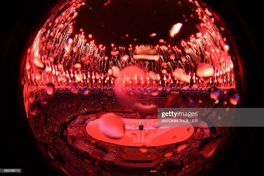 TOPSHOT - This picture shows an overview of the closing ceremony of the Rio 2016 Olympic Games under the rain at the Maracana stadium in Rio de Janeiro on August 21, 2016. / AFP / Antonin THUILLIER