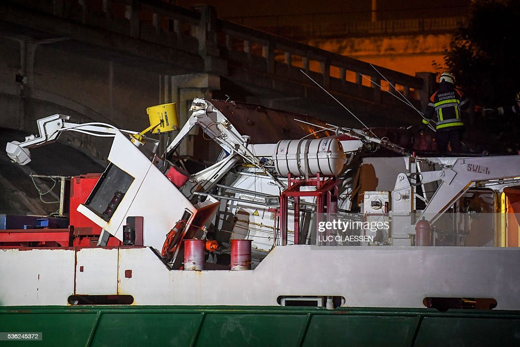 This picture shows firefighters intervening at the scene of an accident where a wood transportation ship hit a bridge over the Albert Canal, early on June 1, 2016 in Antwerpen, in which at least one person was severely injured. The ship's wheelhouse was totally destroyed in the accident that occured late on May 31. / AFP / Belga / LUC CLAESSEN / Belgium OUT