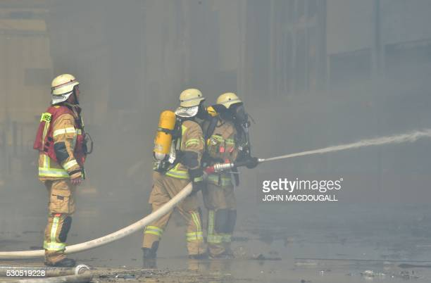 This picture shows firemen at work as smoke billows from a fire in a storage facility at the Dong Xuan shopping centre in Berlin's Lichtenberg...