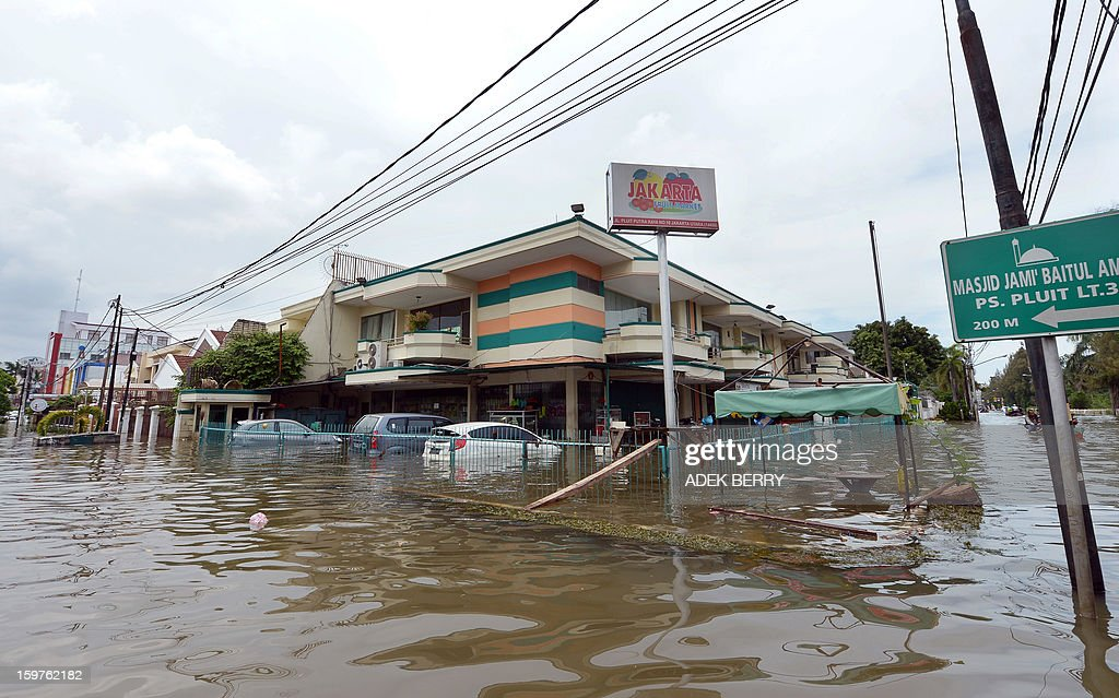 This picture shows houses and cars inundated by floodwaters at a luxury housing complex in Jakarta on January 20, 2013. The death toll from floods in Indonesia's capital Jakarta rose to 15 on January 19 after rescuers found another four bodies. The floods are the worst to hit the capital since 2007 and forced 18,000 people from their homes.